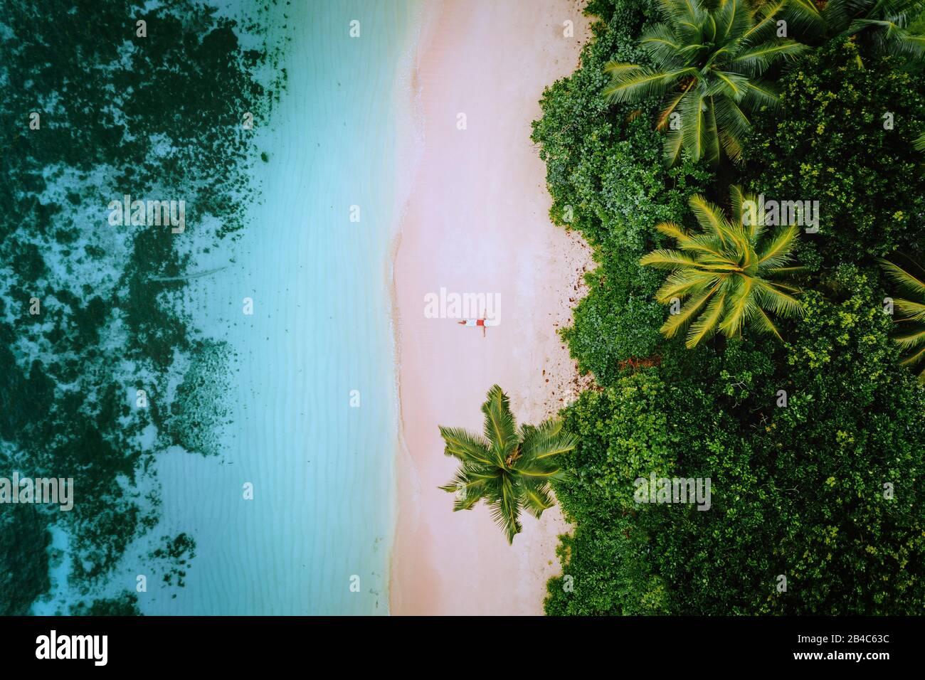 Vista aérea de una joven que se relaja en la playa de arena paradisíaca tropical rodeada de palmeras y aguas cristalinas del océano. Foto de stock
