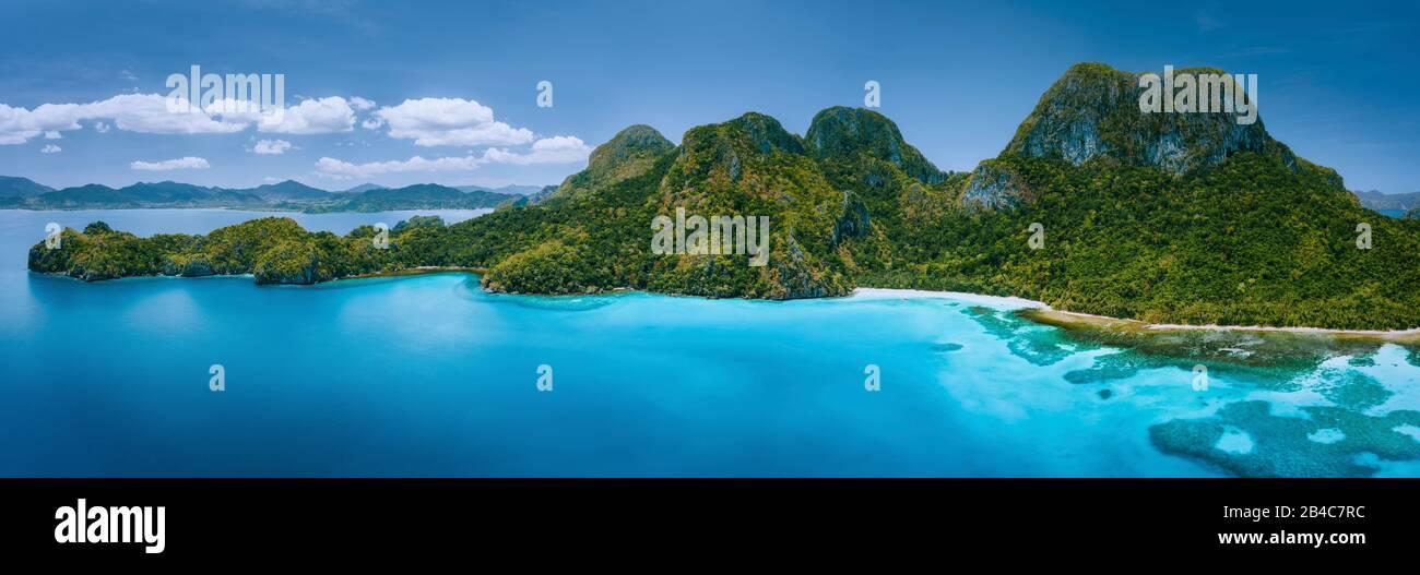 Vista panorámica aérea de drone de isla tropical deshabitada con montañas escarpadas, selva tropical, playas de arena rodeadas por el océano azul. Foto de stock