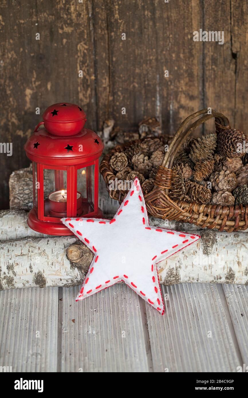 Navidad rústica todavía vida con farol rojo, estrella blanca roja y conos de pino a través de la vieja pared de madera Foto de stock