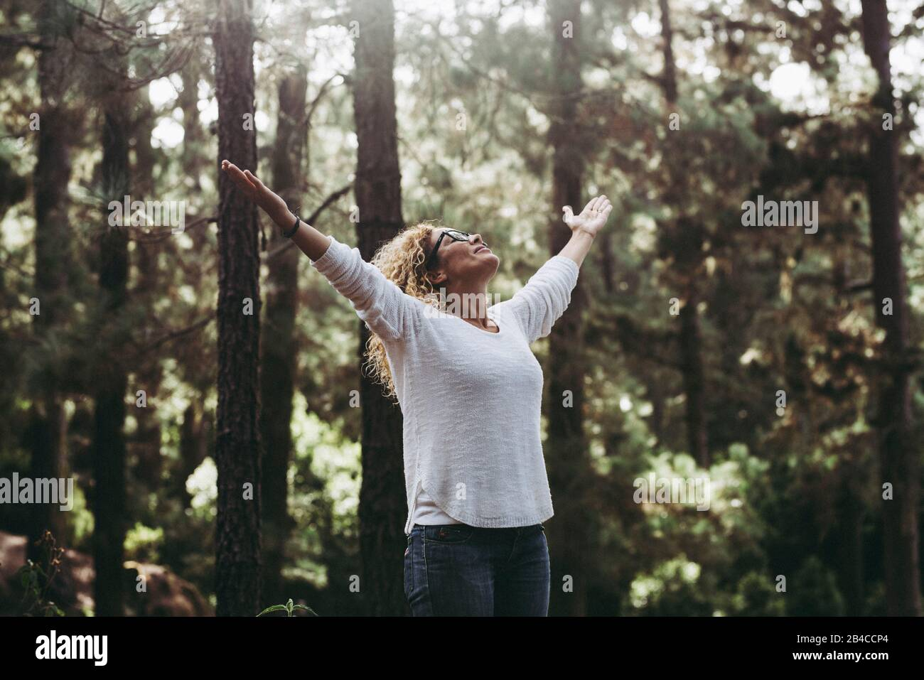 Salvar el planeta para un mejor concepto de futuro limpio y verde - gente caucásica joven mujer abriendo los brazos en el bosque para detener la deforestación y ayudar al mundo Foto de stock