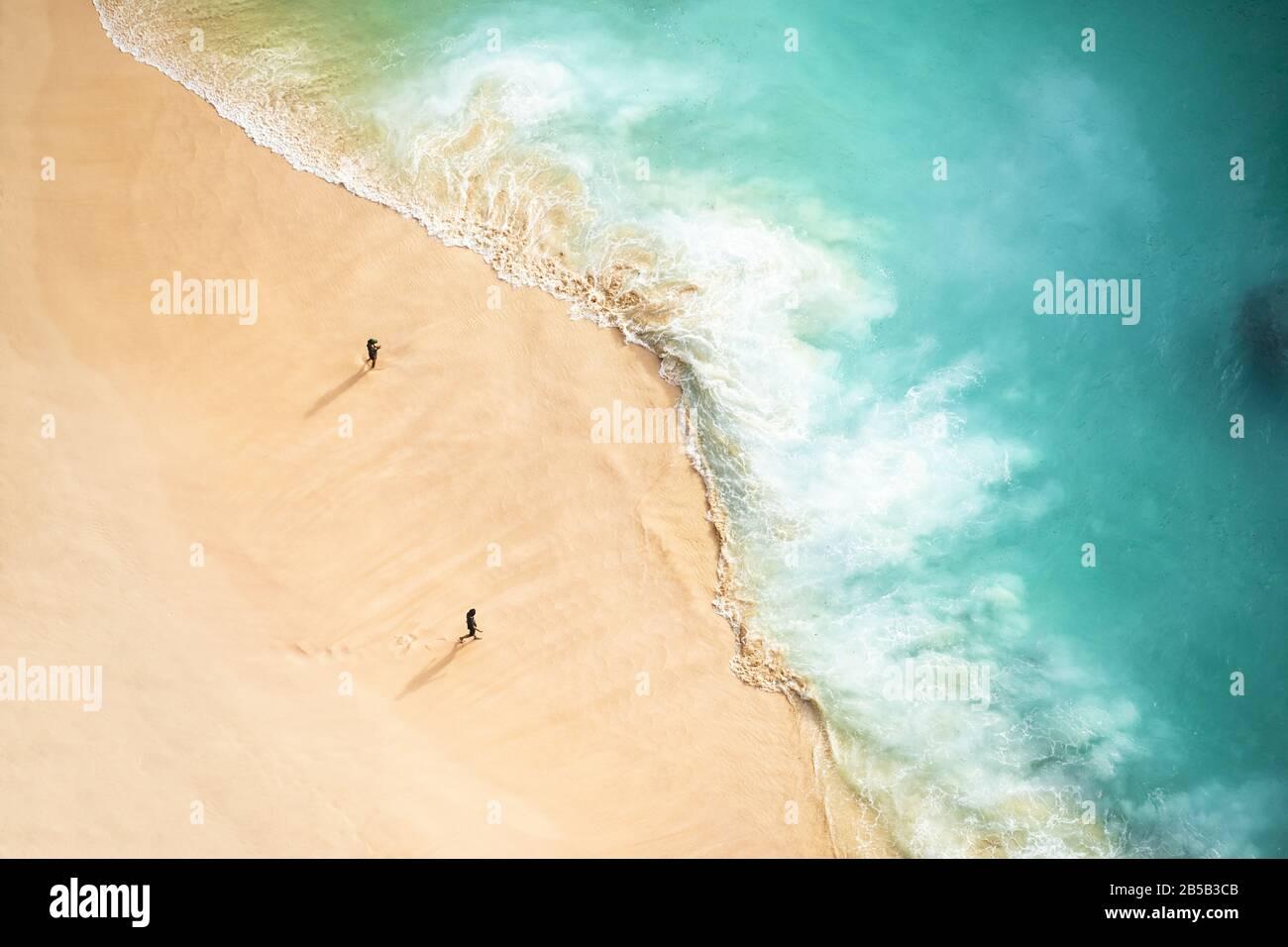 Vista desde arriba, impresionante vista aérea de dos personas caminando en una hermosa playa bañada por un mar turquesa durante la puesta de sol. Foto de stock