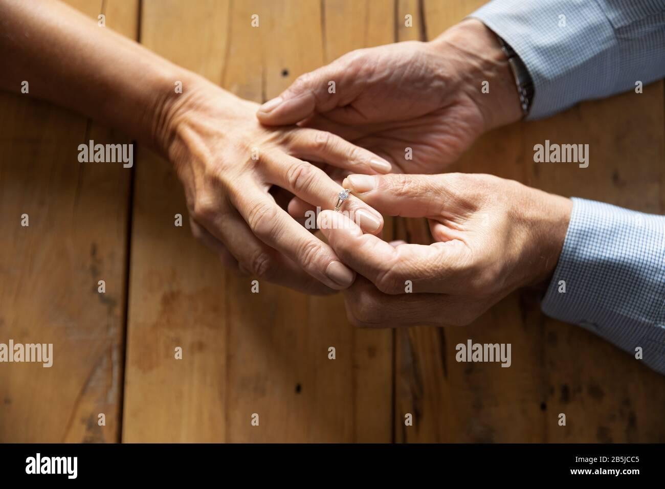 El anciano puso el anillo de boda en la mano de la mujer de mediana edad Foto de stock