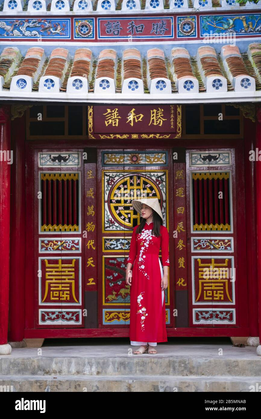 Una joven vietnamita que viste un vestido tradicional de Ao Dai en las calles de la vieja Hoi An Foto de stock