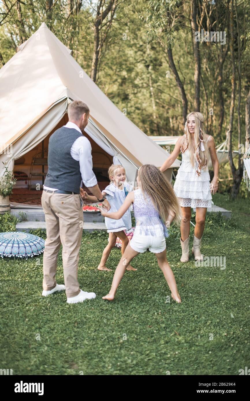 La familia joven está jugando juntos en un día soleado en el parque. Padre, madre y dos hijas en ropa boho casual bailando y saltando, sosteniendo las manos adentro Foto de stock