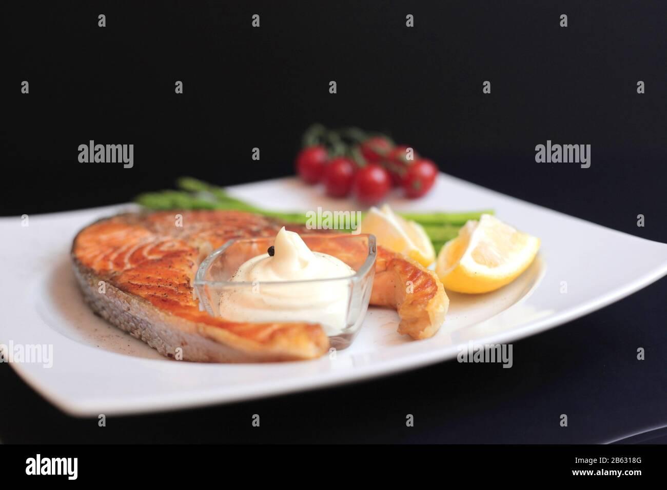 filetes de salmón con verduras y especias: espárragos, tomates, jengibre, pimentones, sal, chile, cebolla, limón y aceite de oliva sobre fondo negro. Sane Foto de stock
