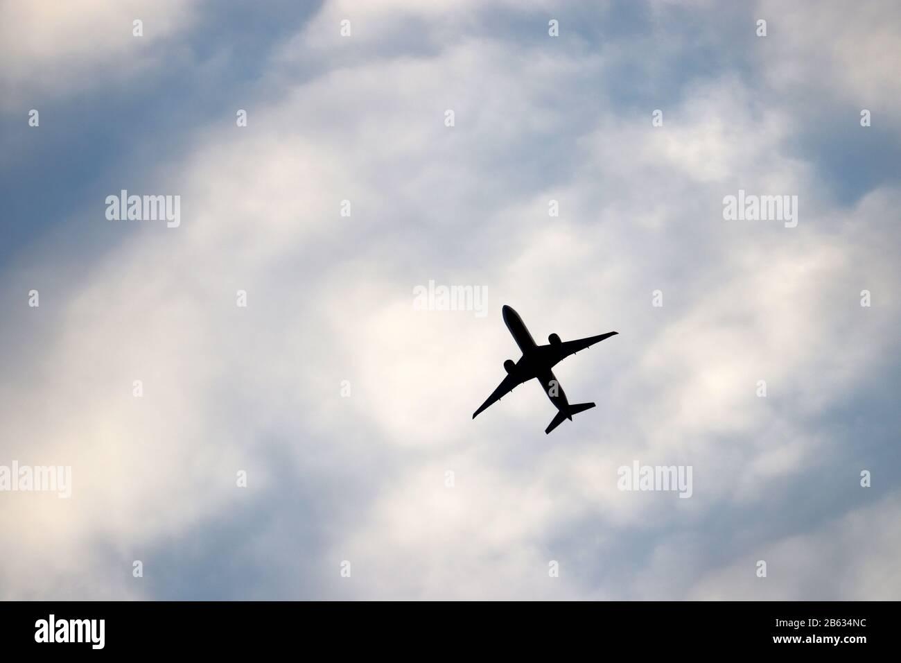Avión volando en el cielo azul sobre el fondo de nubes blancas. Silueta de un avión comercial durante el concepto de ascenso, desplazamiento y turbulencia Foto de stock