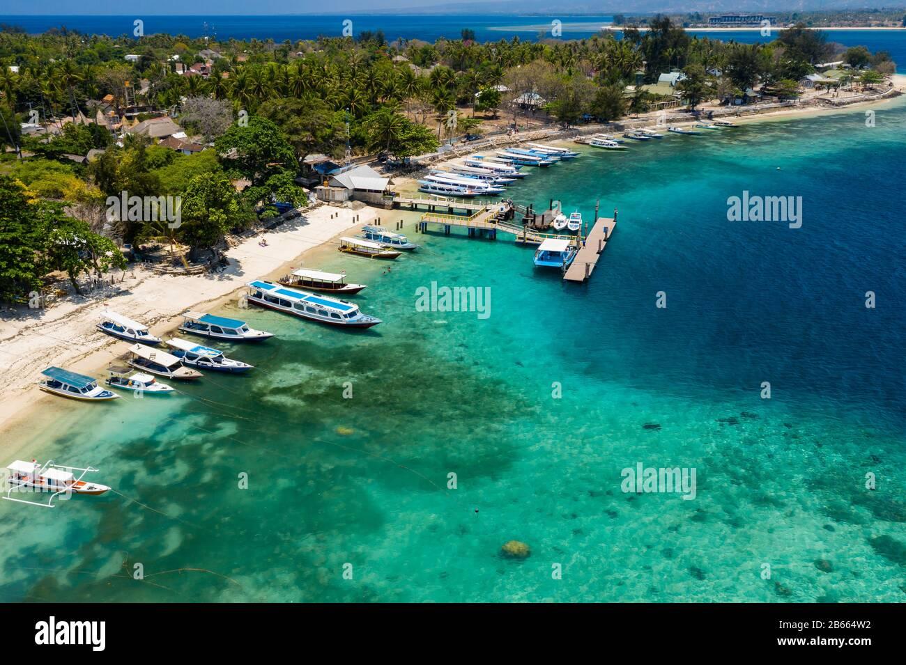 Vista aérea de barcos amarrados en un hermoso arrecife de coral tropical y la playa en una pequeña isla (Gili Air, Indonesia) Foto de stock
