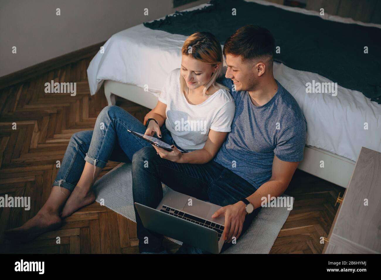 Vista superior de una pareja caucásica sentada en el suelo y usando aparatos modernos mientras sonríe y disfruta Foto de stock