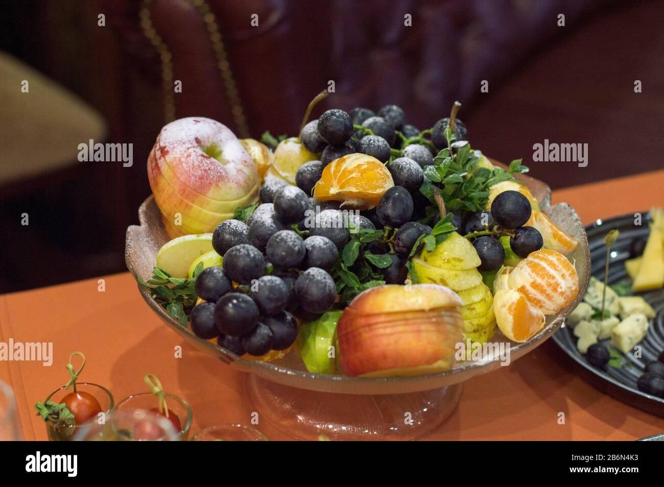 Jarrón con frutas sobre la mesa. and en rebanadas cocinadas para la cena. Foto de stock