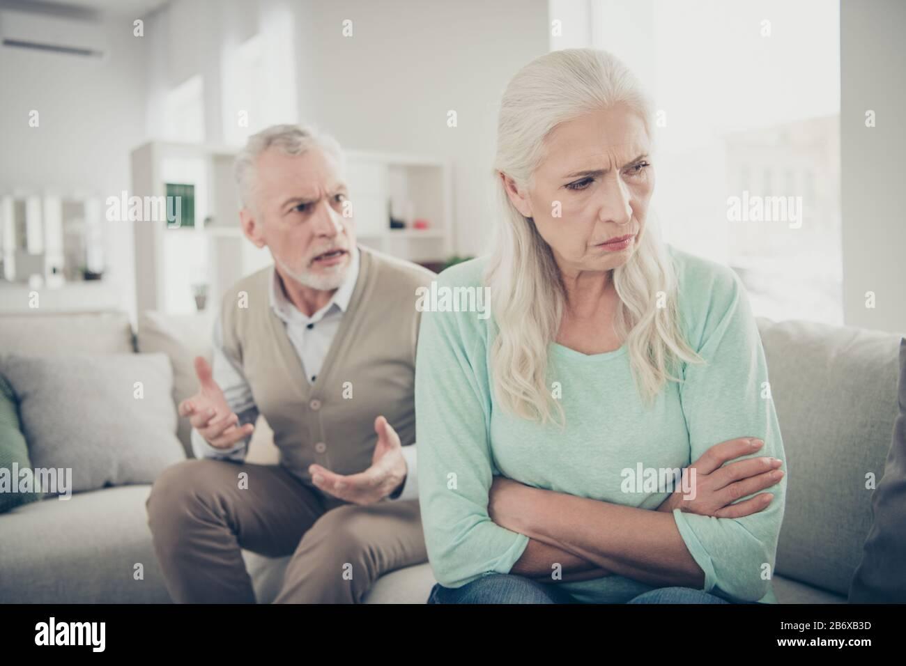 Foto de cerca de la vieja abuela triste y de pelo largo no quiere escuchar a su marido estricto que está enviando reclamaciones Foto de stock