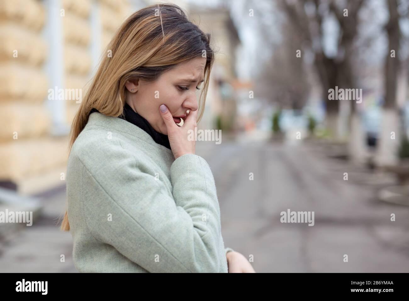 Deprimida mujer triste de perfil casi llorando en una calle de la ciudad en Europa, mirando hacia abajo, llorando debido a su traición novio Foto de stock