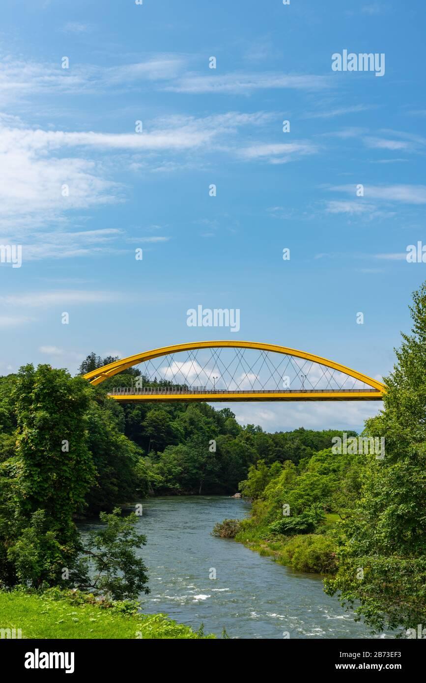 Puente de Niseko en la primavera, un puente amarillo que atraviesa la línea principal de Hakodate y el río Shiribetsu Foto de stock