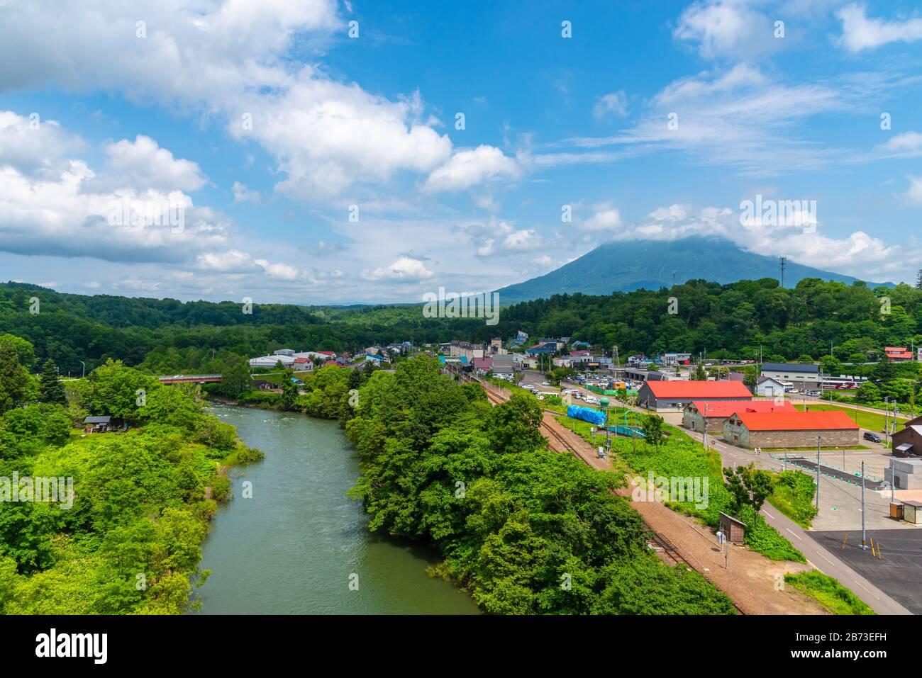 Paisaje urbano de Niseko en primavera soleado día con el Monte Yotei en el fondo. Una ciudad situada en la Subprefectura de Shiribeshi Foto de stock