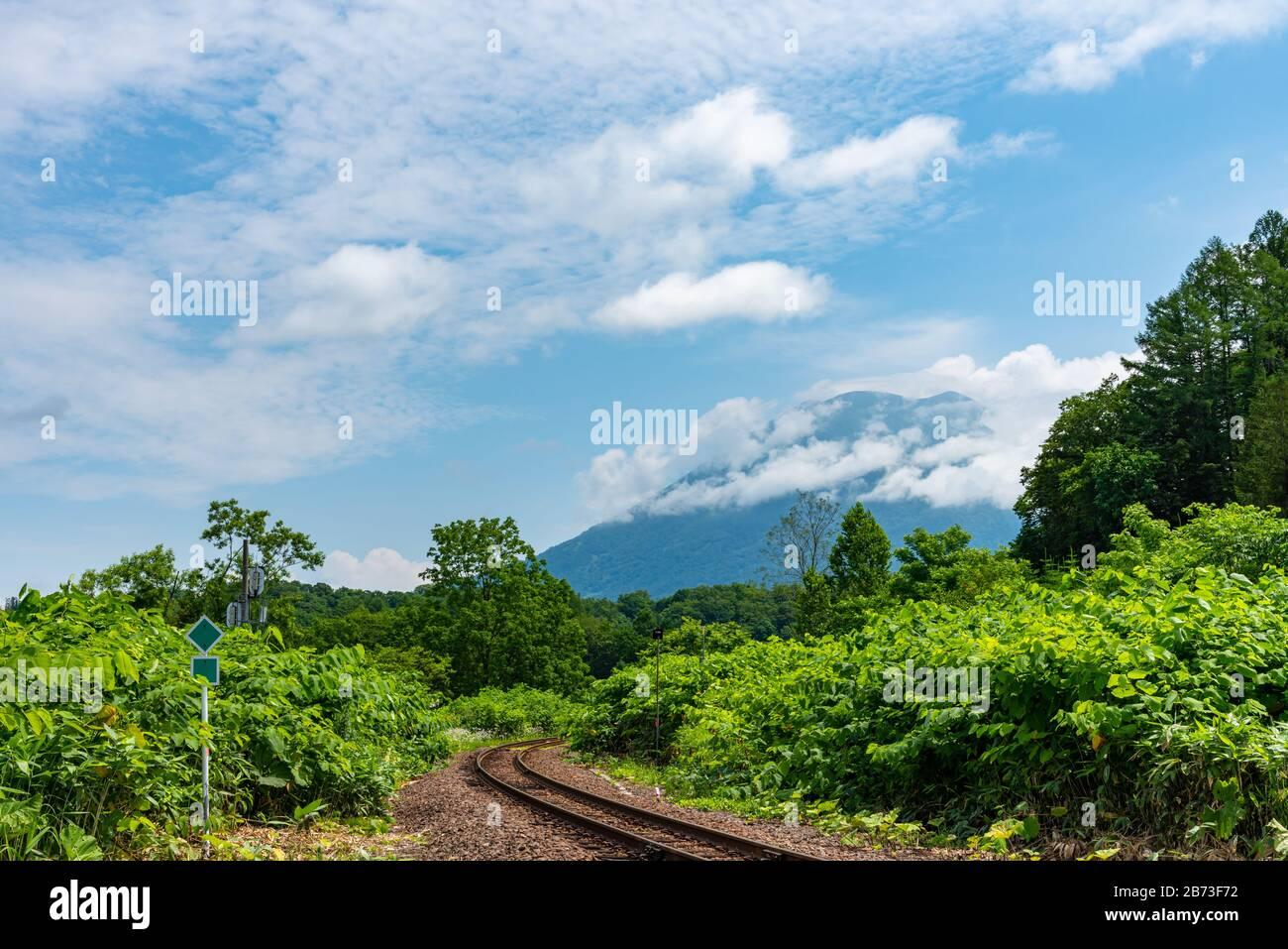 Hakodate línea principal de ferrocarril en la ciudad de Niseko en primavera soleado día con el Monte Yotei en el fondo. Subprefectura de Shiribeshi, Hokkaido, Japón Foto de stock