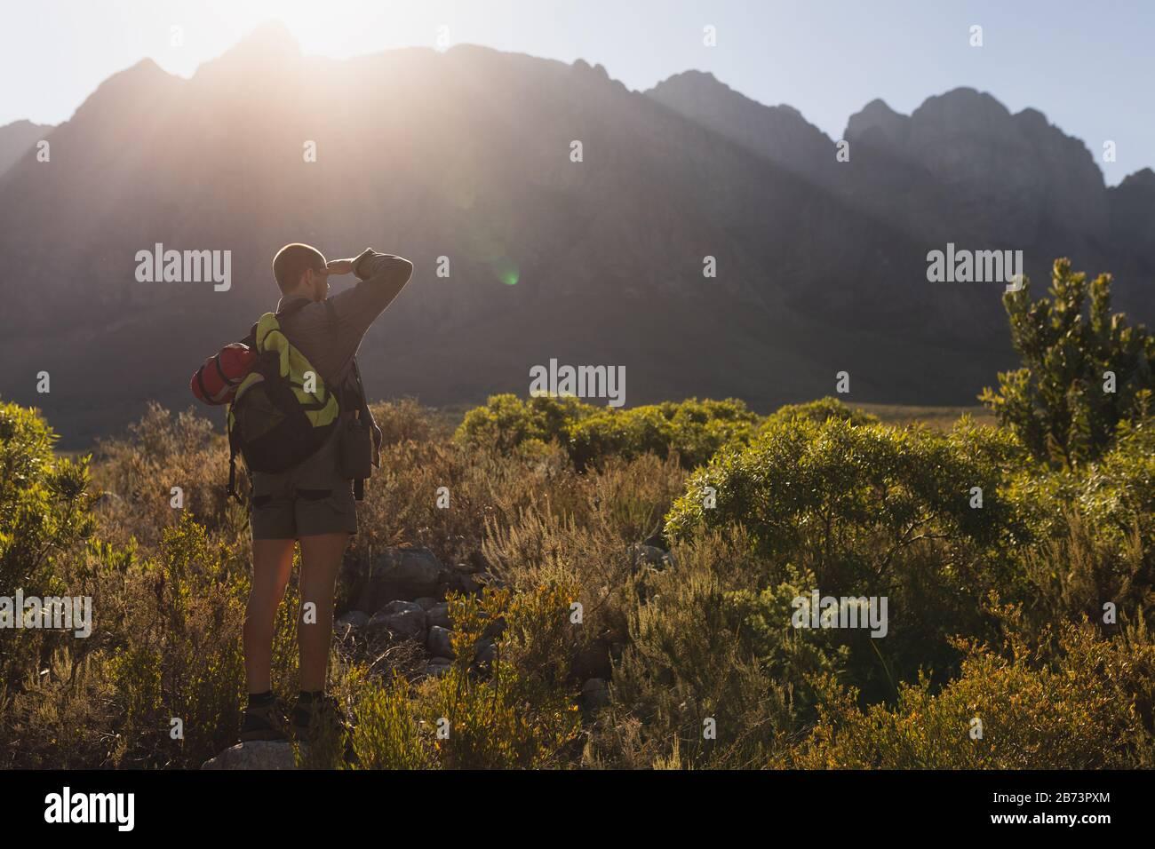 Vista trasera del hombre en una roca mirando hacia fuera Foto de stock
