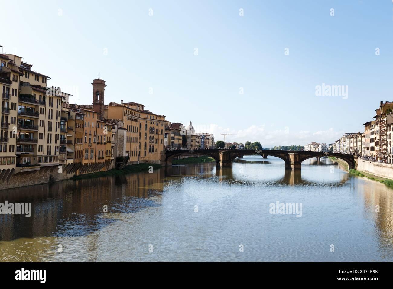 Calles con casas antiguas de colores y puentes en el centro de Florencia Foto de stock