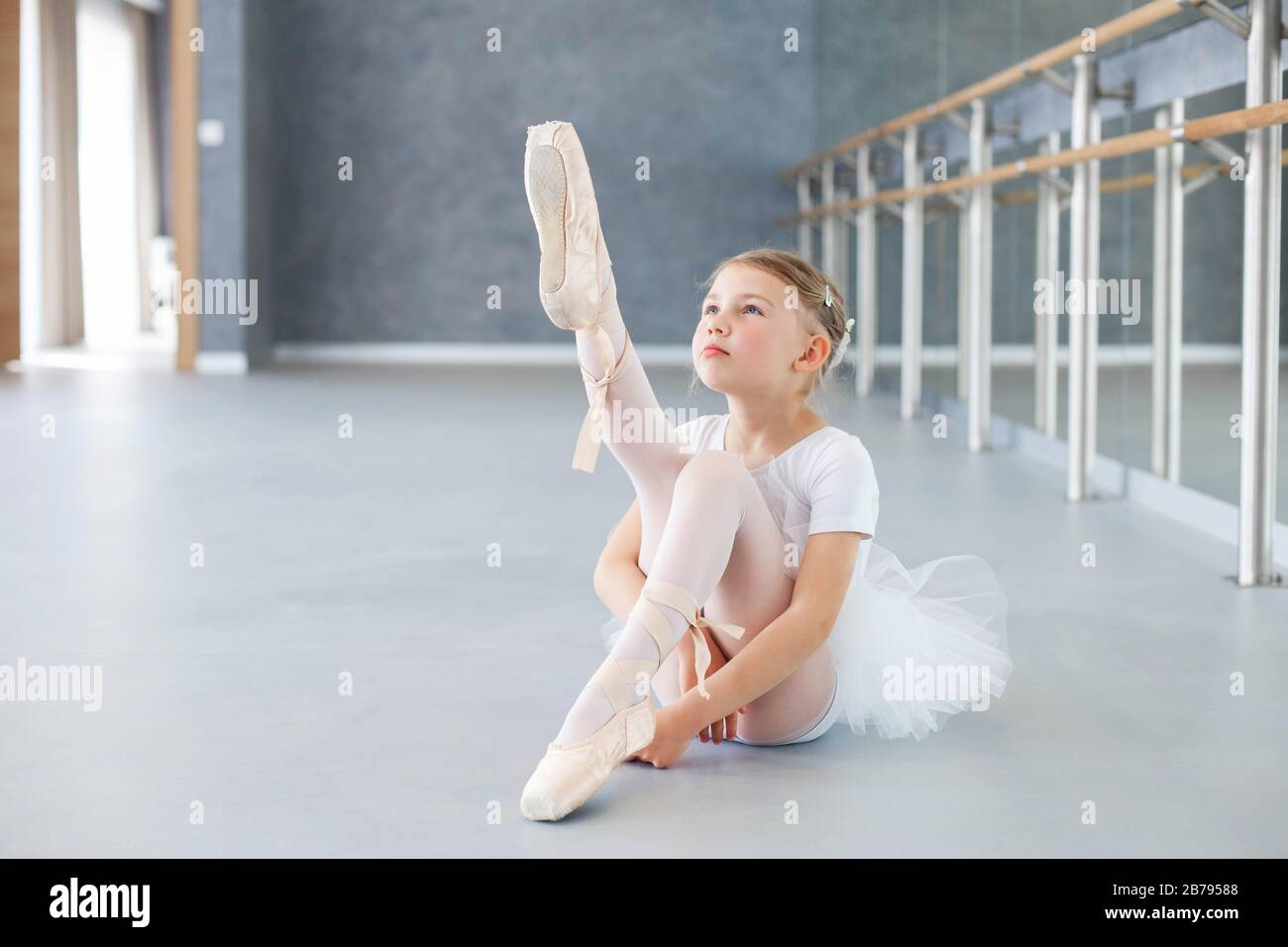 La bailarina pequeña está intentando en zapatos de la punta en la clase del ballet. Linda niña está sentada en el suelo bajo barre Foto de stock