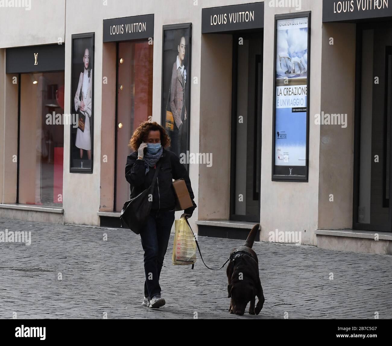Berlín, Marzo De 12. 15 de marzo de 2020. Una mujer con una máscara de cara camina un perro en la calle comercial Via dei Condotti en Roma, Italia, el 12 de marzo de 2020. PARA IR CON LOS TITULARES DE XINHUA DEL 15 DE MARZO DE 2020. Crédito: Elisa Lingria/Xinhua/Alamy Live News Foto de stock