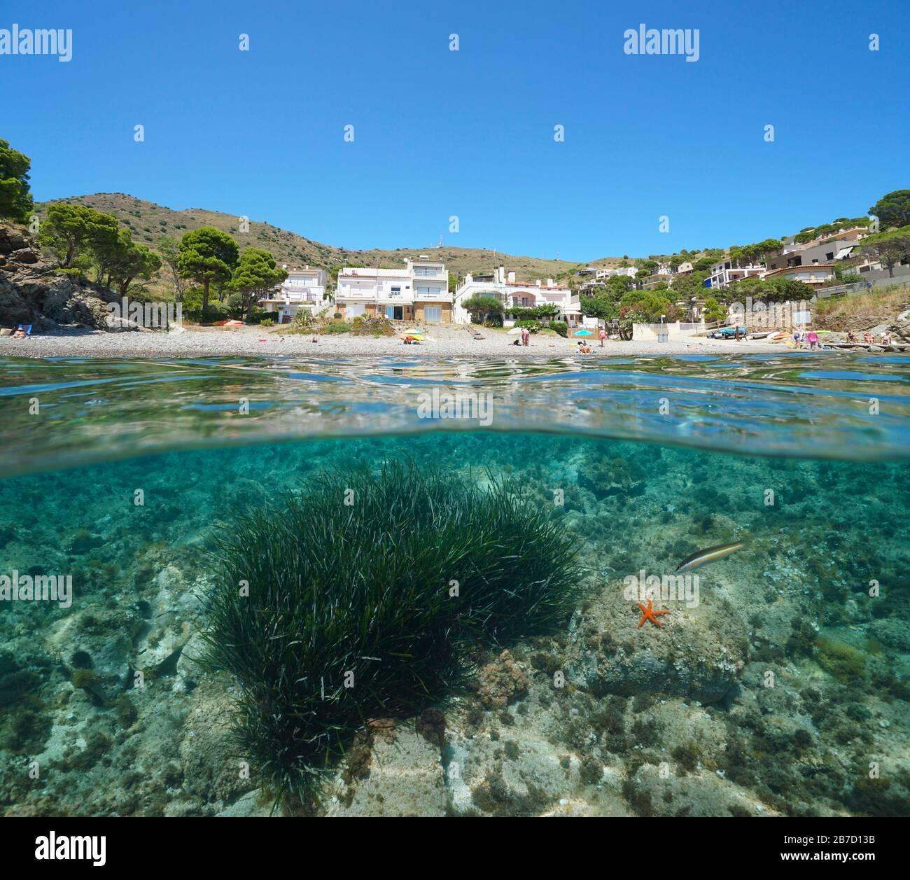 España vacaciones de verano mar Mediterráneo, costa de playa con edificios, vista dividida sobre y debajo de la superficie del agua, Costa Brava, Colera, Cataluña Foto de stock