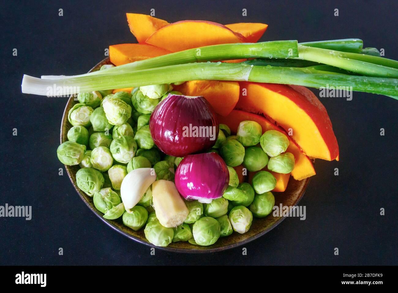 Plato con una colorida variedad de verduras frescas: Coles de Bruselas, cebollas rojas, cebolletas, calabaza, ajo y jengibre. Fondo negro. Foto de stock