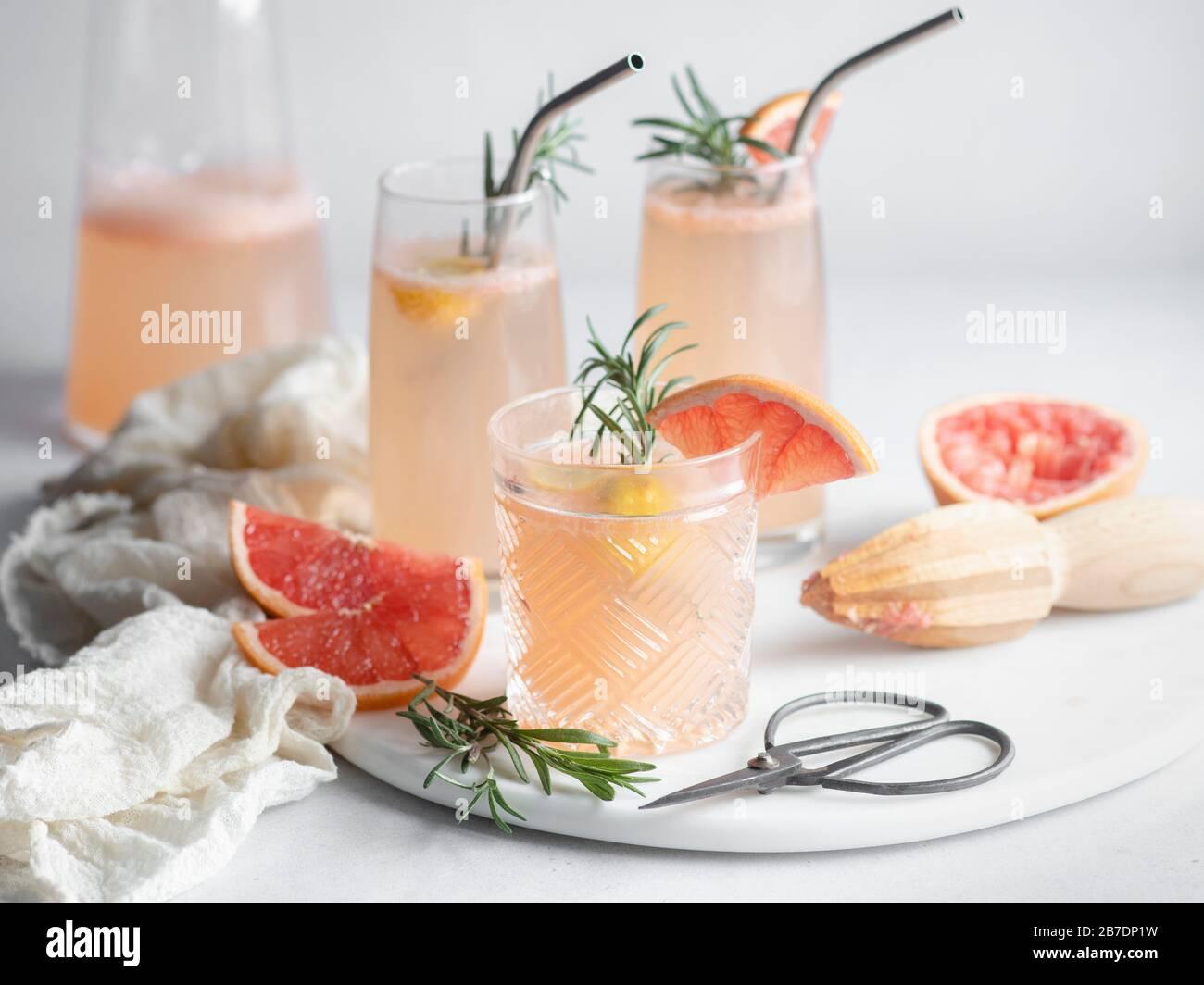 3 vasos de cóctel de pomelo en una bandeja de mármol con romero y rodajas de pomelo, jarra y servilleta de mousselina Foto de stock
