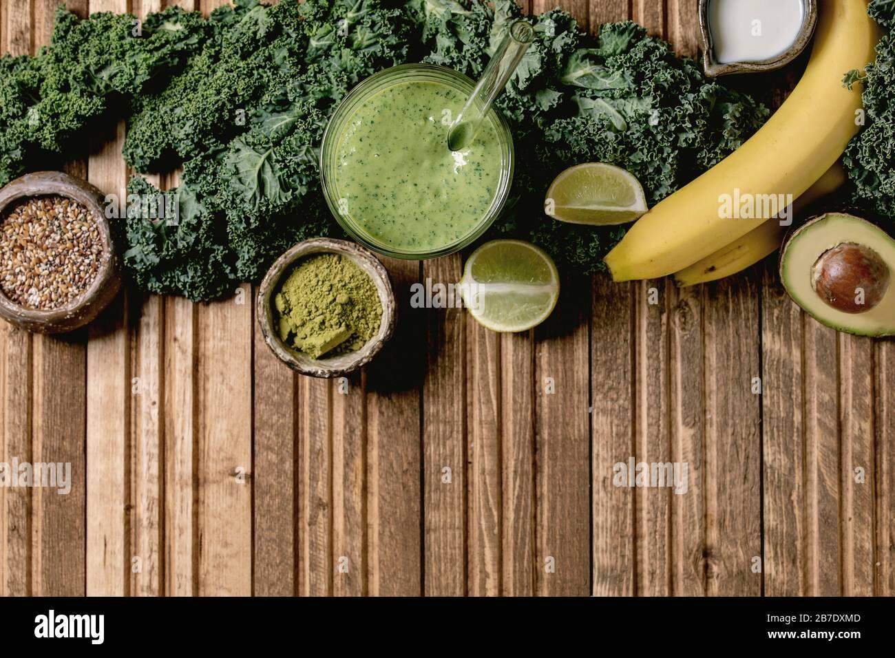 Cristal de verde saludable vegano batido, paja de vidrio. Ingredientes arriba. Kale, plátanos, aguacate, lima, leche no diaria, polvo de matcha y semillas sobre madera Foto de stock