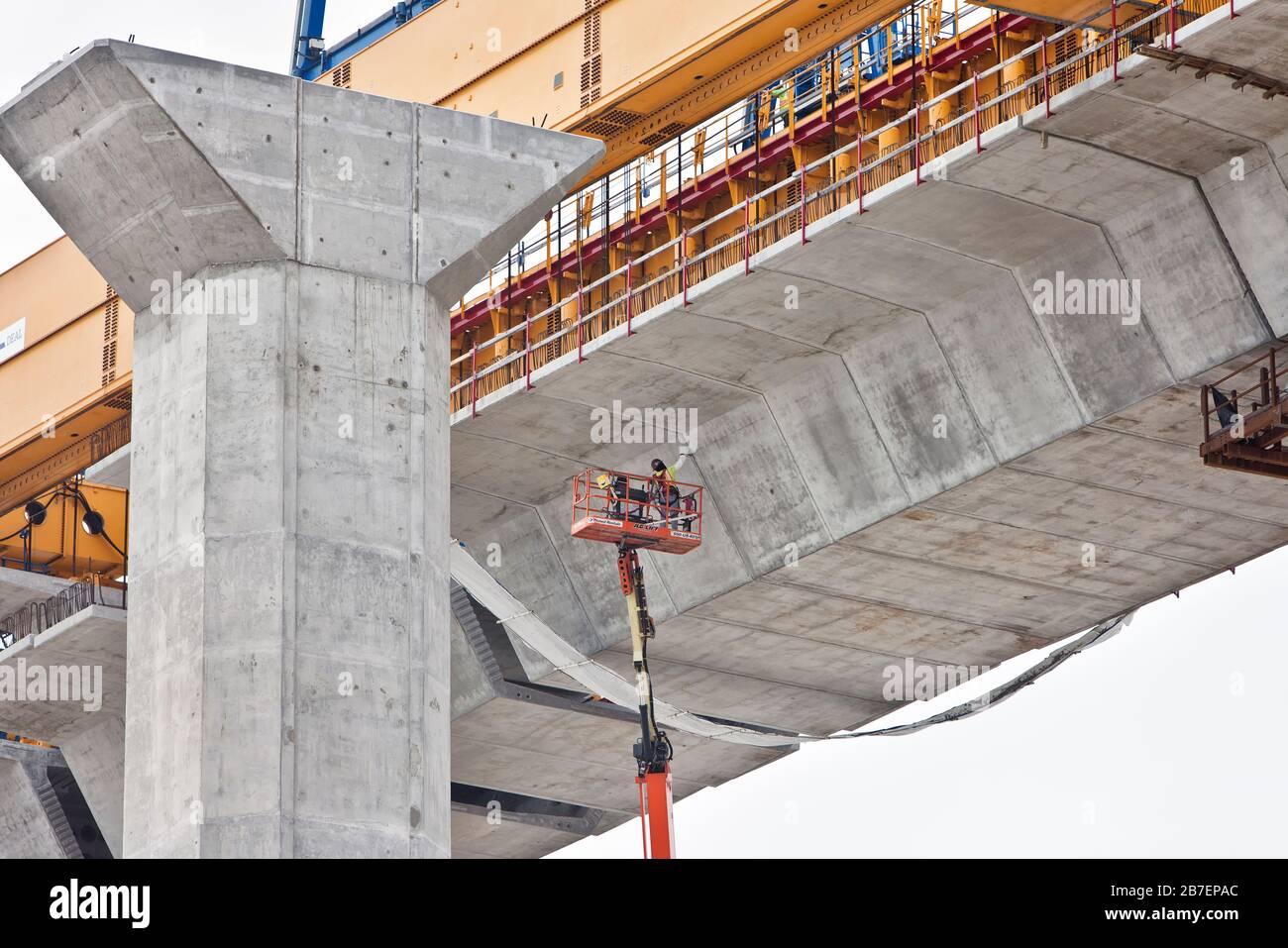 Construcción del puente New Harbor, trabajador suspendido con el elevador de fuerza extendido, limpiando juntas de cemento debajo del puente. Foto de stock