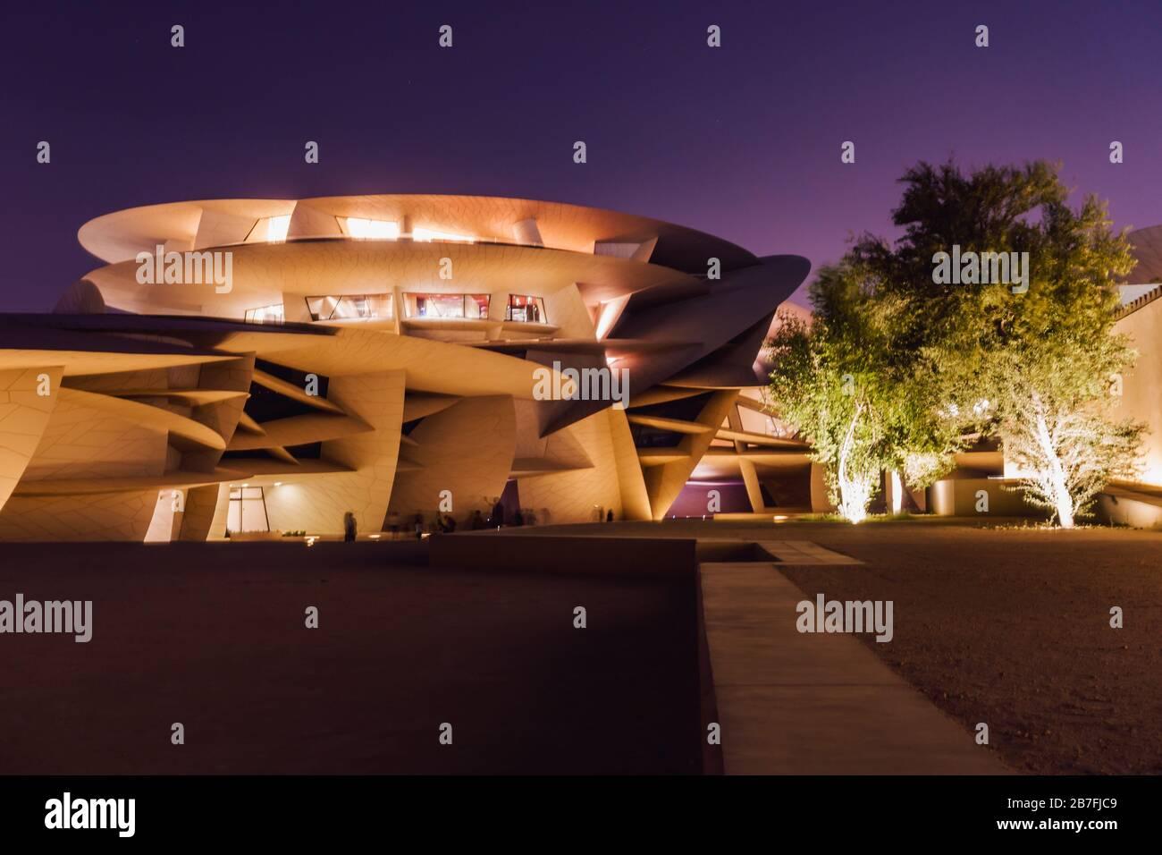 Foto nocturna del Museo Nacional de Qatar, con su llamativo diseño en disco, en Doha, Qatar Foto de stock