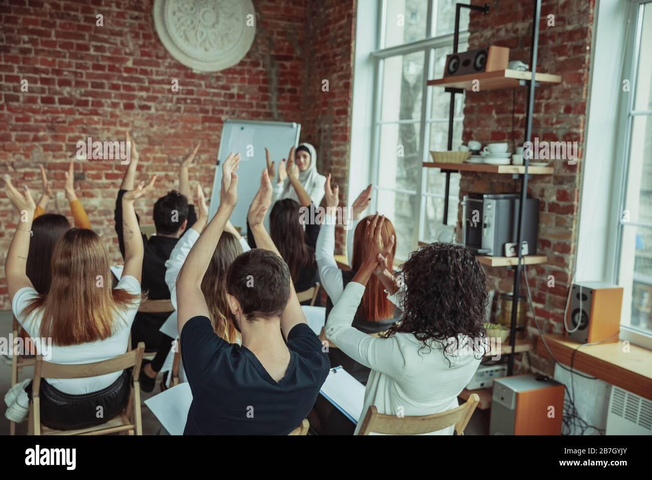 Una oradora musulmana que da una presentación en el salón del taller. Audiencia o sala de conferencias. Los participantes aplauden a la audiencia. Evento de conferencia, formación. Educación, diversidad, concepto inclusivo. Foto de stock