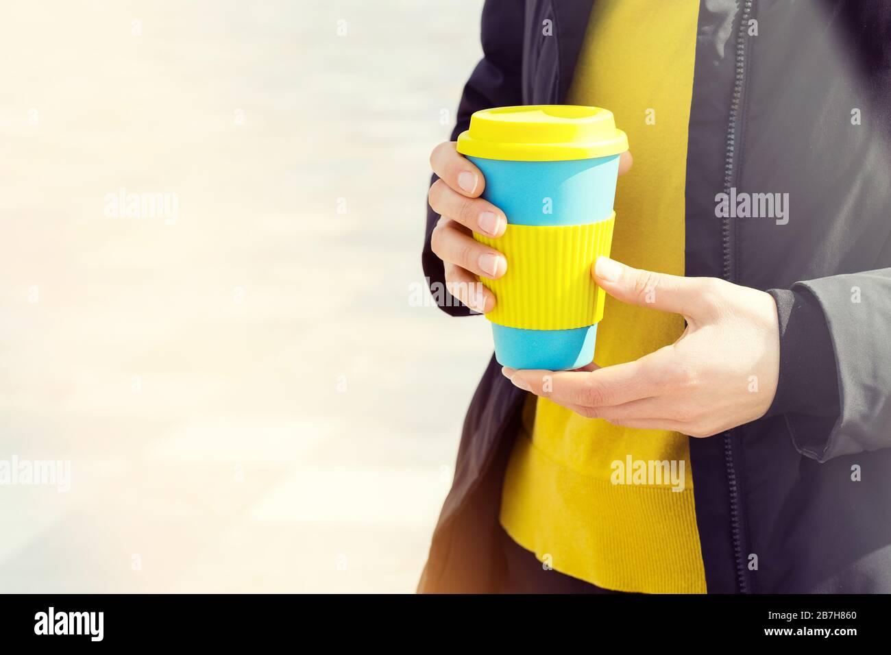 Taza de café reutilizable con las manos femeninas. Llévate el café a cualquier parte con una taza reutilizable. Foto de stock