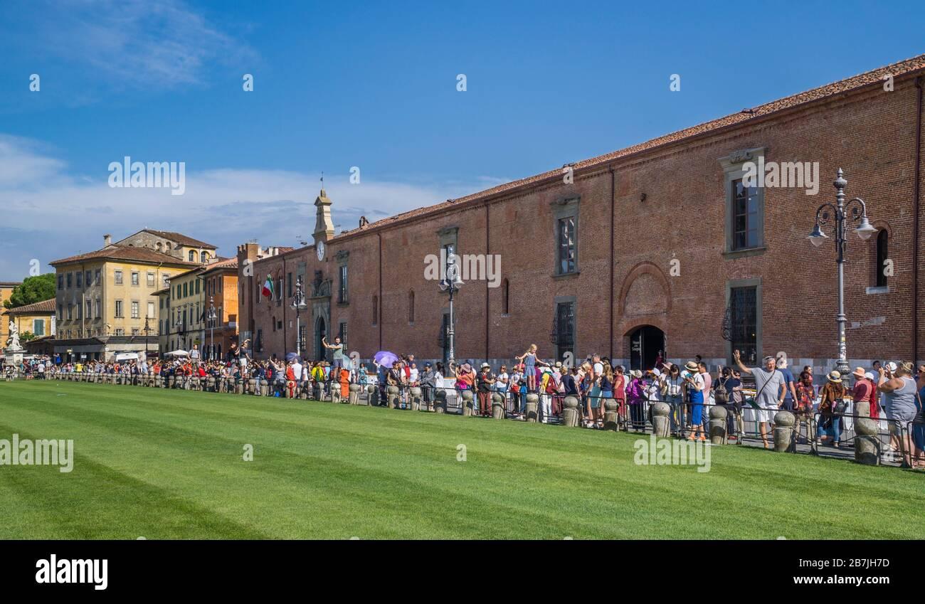 Los turistas admirando la Torre inclinada de Pisa desde la posición estratégica populat en el borde de la Piazza dei Miracoli en Ospedale Nuovo di Santo Spirito, Pisa, tu Foto de stock