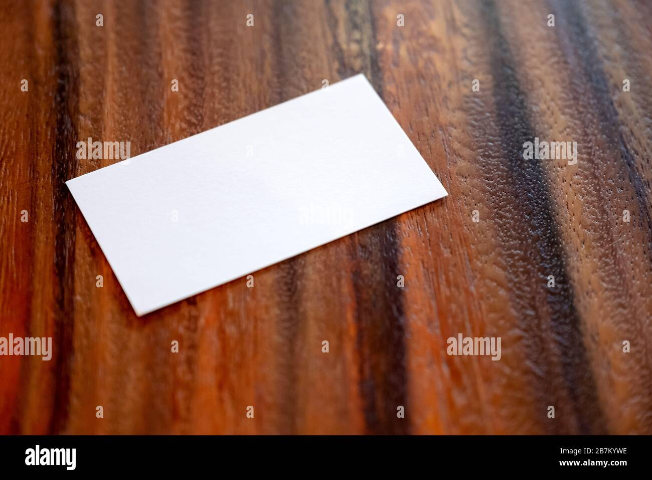 Una tarjeta de visita blanca en blanco sobre fondo de madera vintage Foto de stock