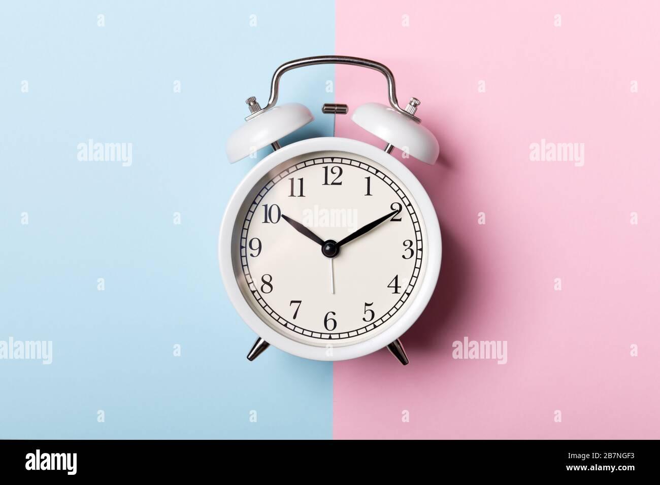 Reloj despertador blanco vintage sobre fondo azul y rosa. Concepto de tiempo Foto de stock