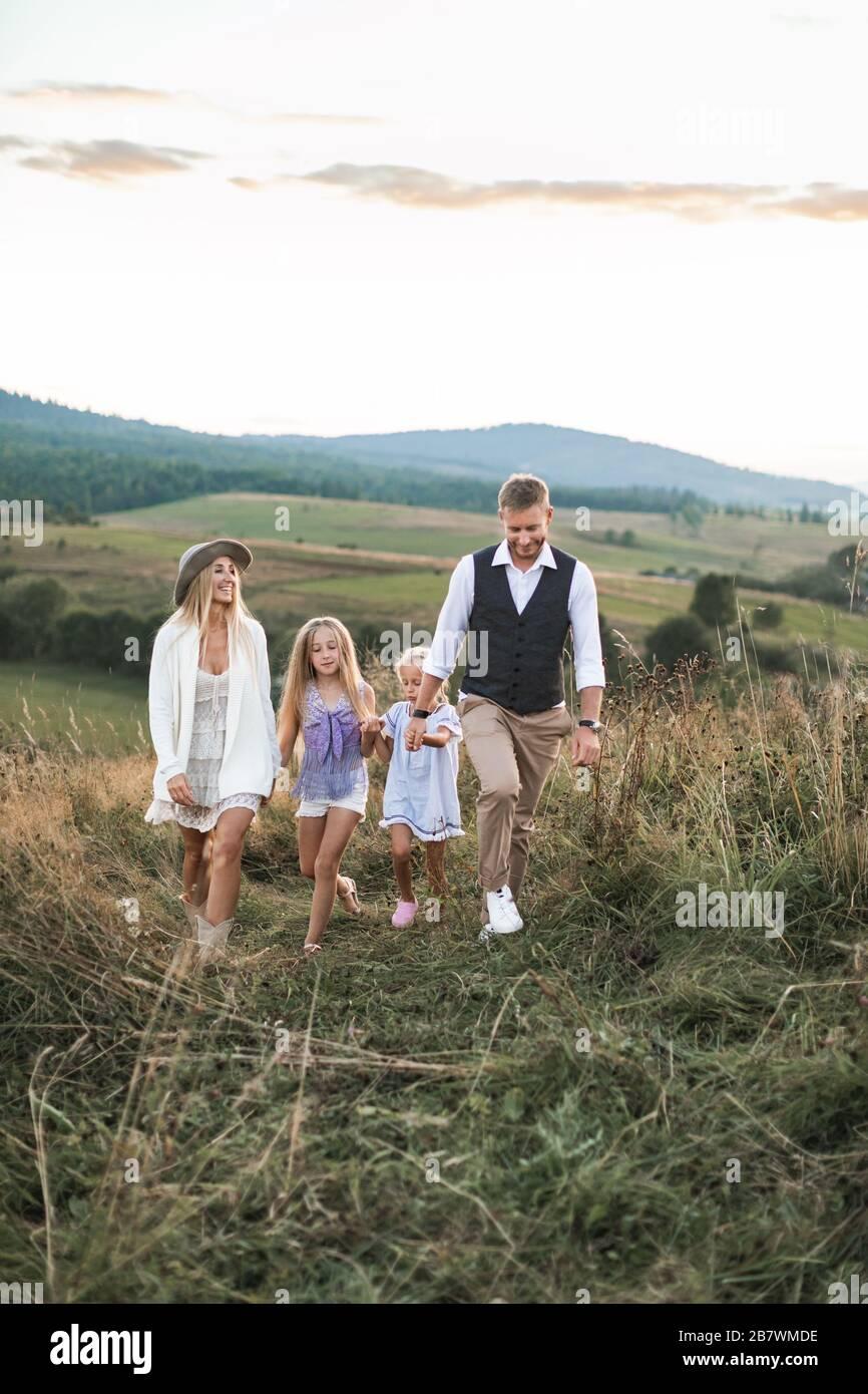 Feliz familia en ropa informal, madre, padre y dos hijas pequeñas en la naturaleza, caminar toethr con las manos, su mer puesta de sol en el campo salvaje en Foto de stock