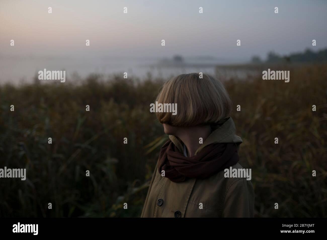Mujer joven en el campo junto al lago al atardecer Foto de stock