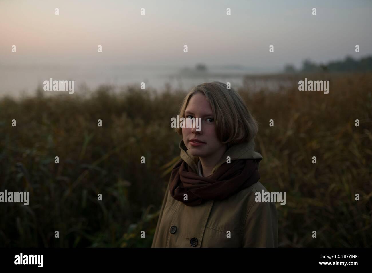 Mujer joven en el campo al atardecer Foto de stock
