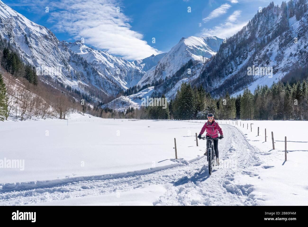 Mujer mayor agradable montando su bicicleta de montaña eléctrica en un soleado día de invierno en los alpes de Allgau cerca de Oberstdorf, Baviera, Alemania Foto de stock
