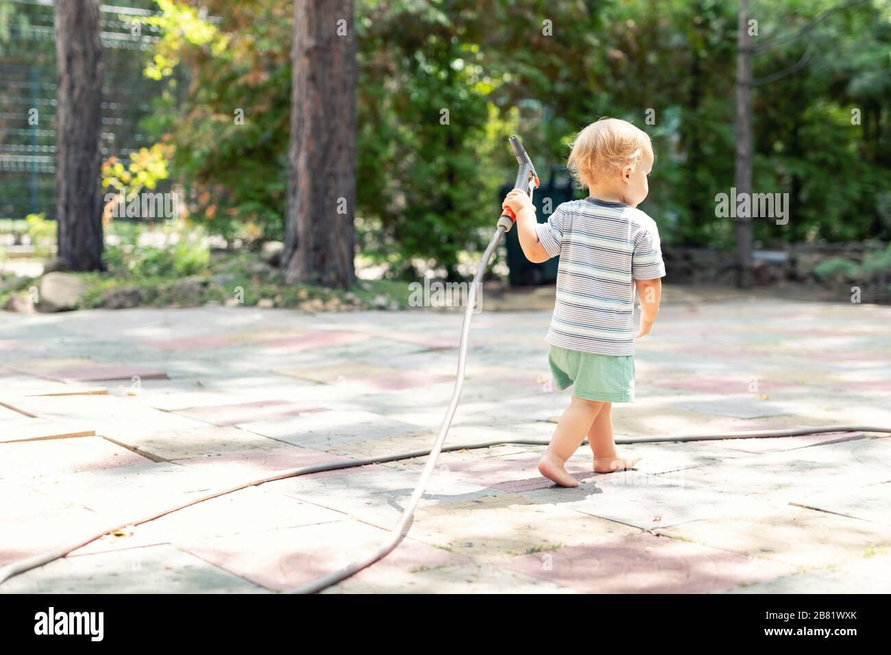 Cute adorable rubia caucásica barefeet muchacho caminando en casa patio tubo sujetando la manguera para regar el jardín. Niño pequeño ayudante jugando en jardinería Foto de stock