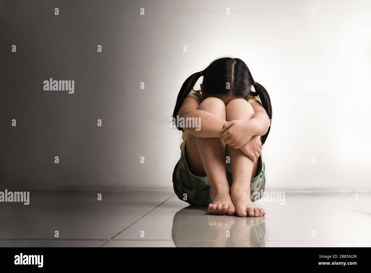 Solos y asustados, niños deprimidos tristes llorando en el cuarto oscuro después de ser intimidados Foto de stock