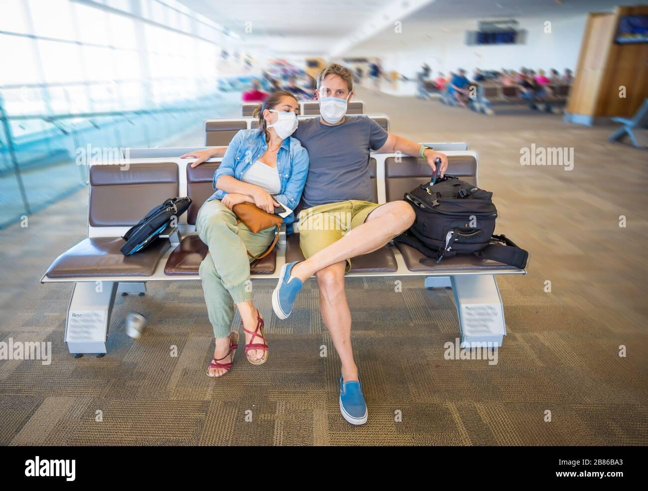 Restricciones de viaje por brote de coronavirus. Los viajeros con máscara en el aeropuerto internacional afectados por las cancelaciones de vuelos y la prohibición de viajar. COVID-19 Foto de stock