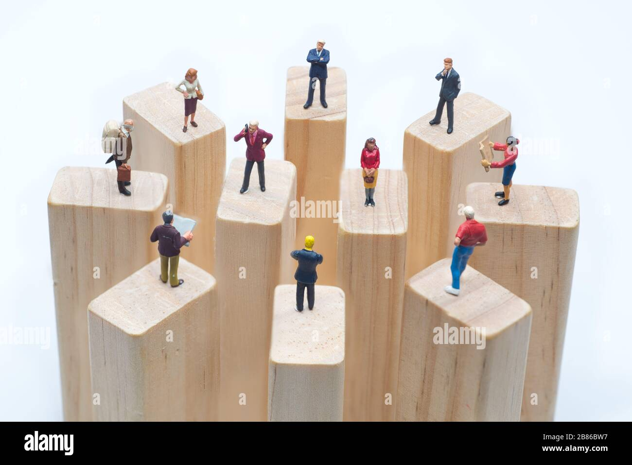 Juguetes en miniatura de pie sobre bloque de madera - concepto de distanciamiento social, antisocial o de trabajo en equipo. Foto de stock