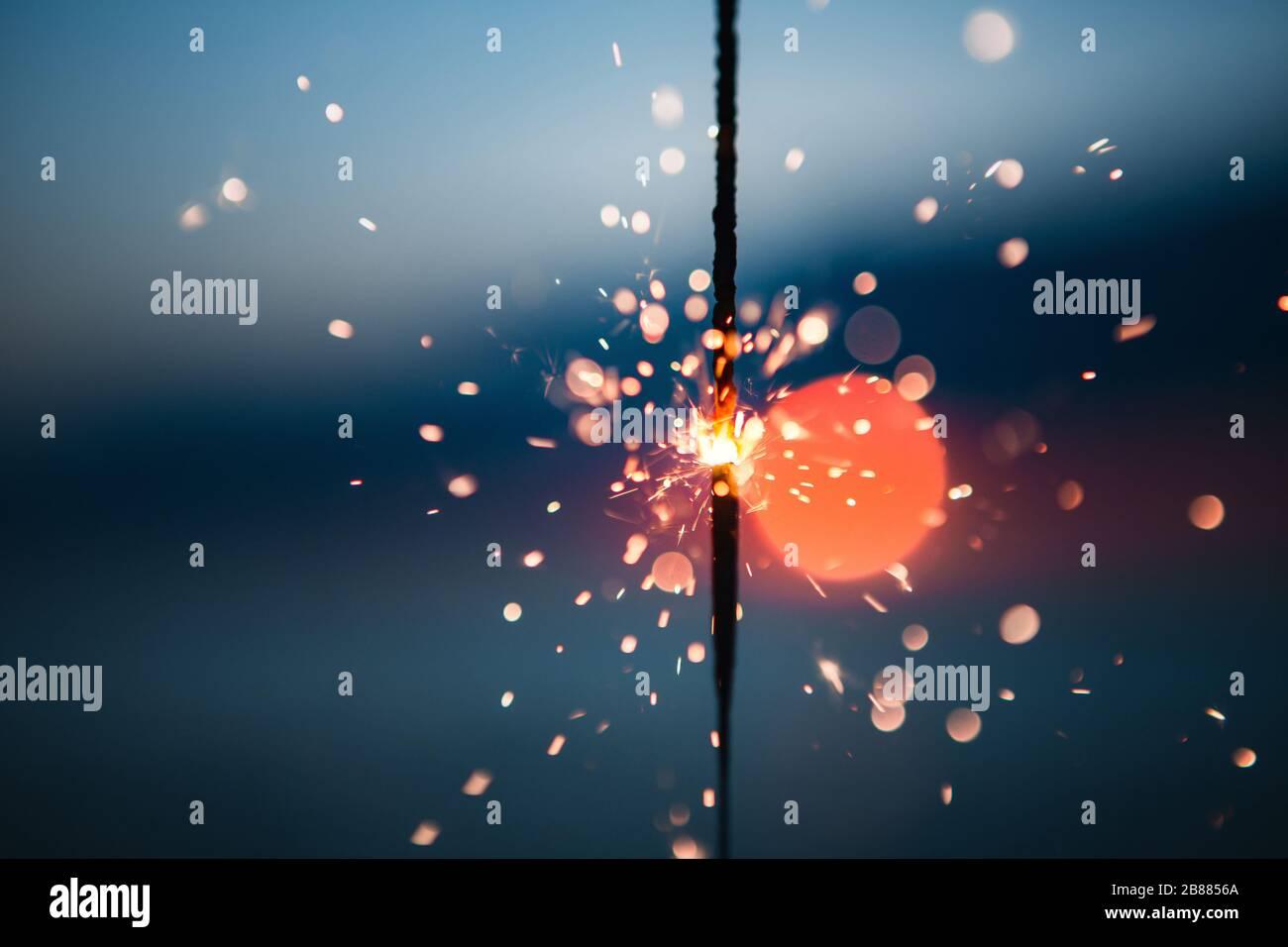 Iluminando una celebración Sparkler del 4 de julio en una playa al atardecer Foto de stock