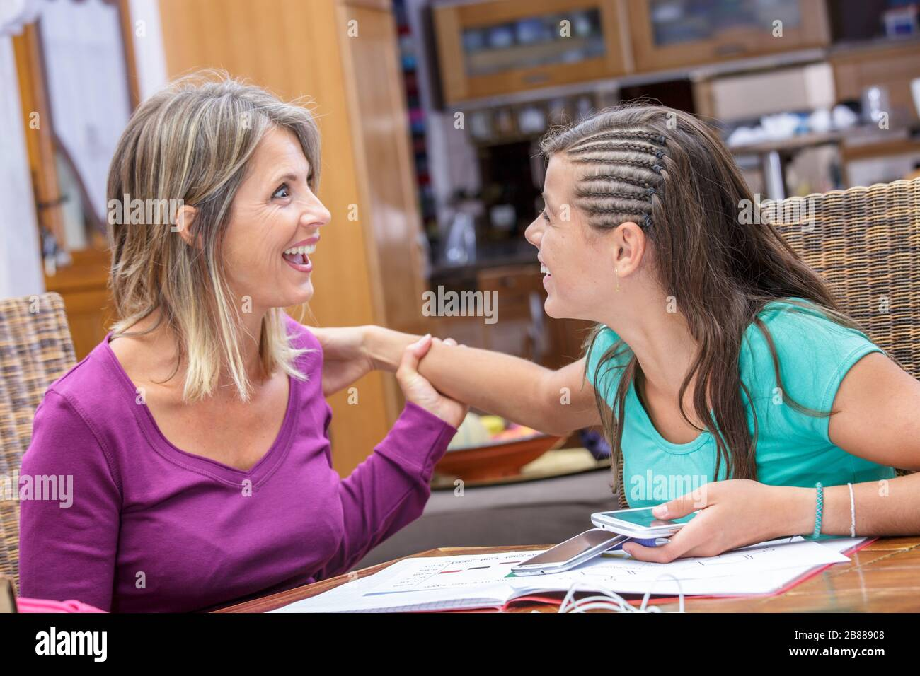 madre e hija compartiendo un momento de complicidad y risa Foto de stock