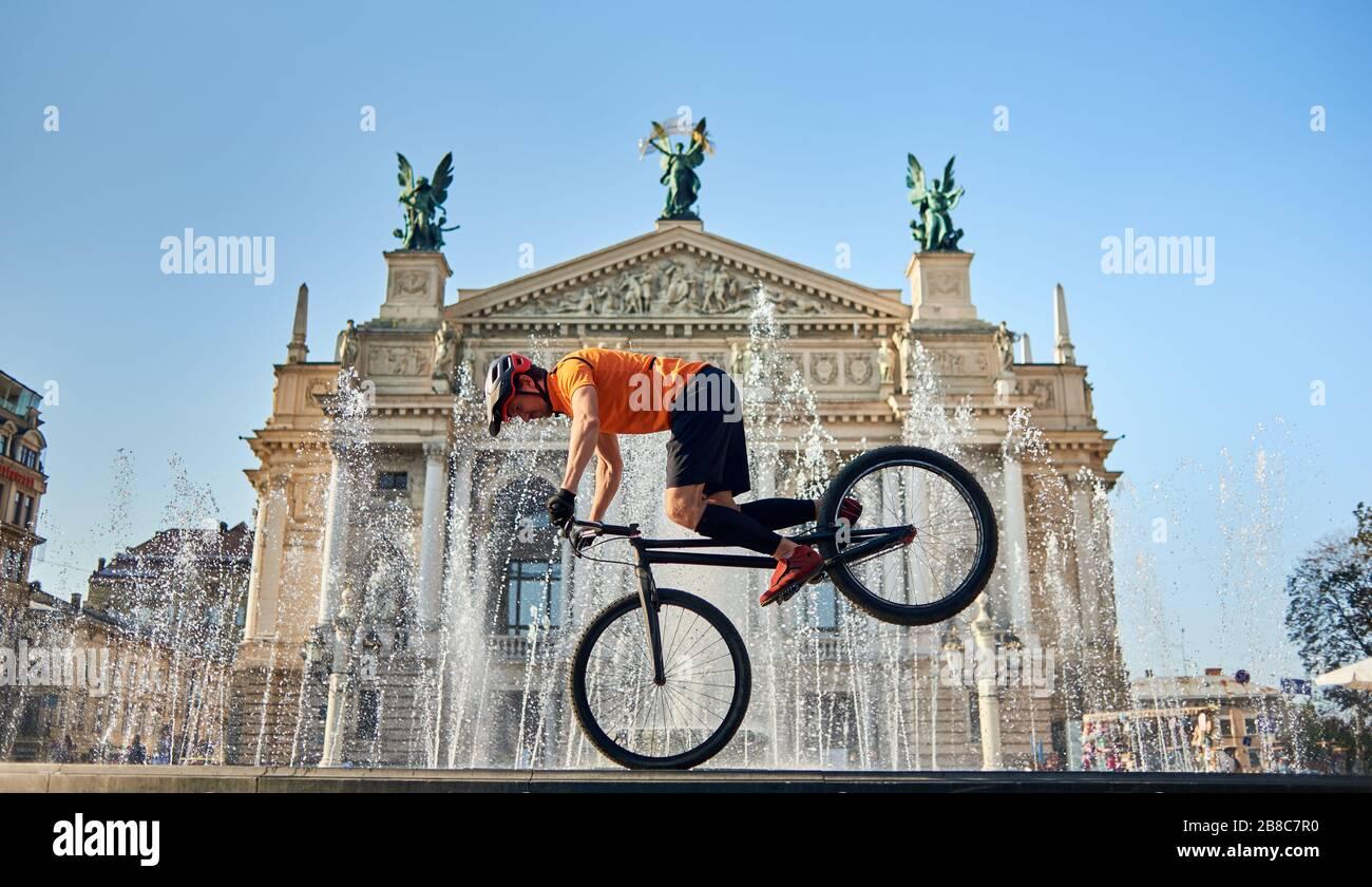 Vista frontal del ciclista parado en la rueda delantera de la bicicleta de montaña y mirando hacia abajo. El joven atleta está montando en bicicleta en el centro cerca de la fuente. Concepto de activo. Foto de stock
