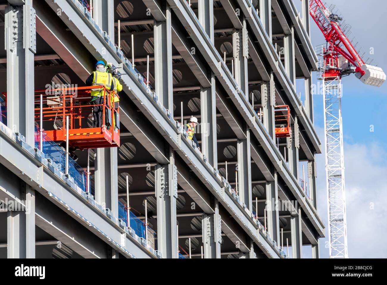 Los trabajadores de la construcción en Glasgow siguen trabajando a través del brote de Coronavirus en Escocia, incluso cuando otros negocios cierran. Foto de stock