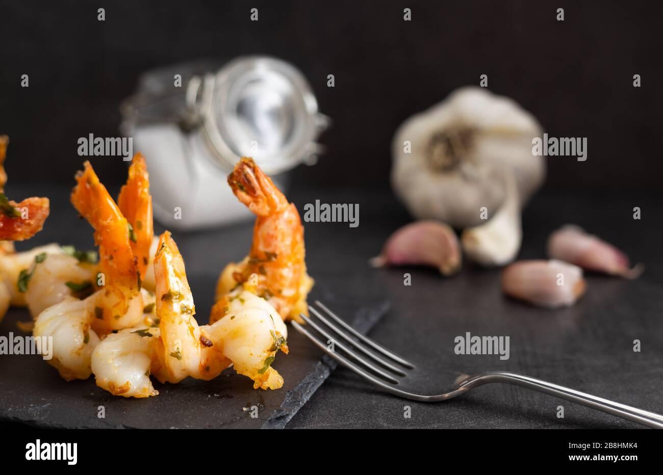 Deliciosos mariscos. Langostinos caseros con salsa de ajo en un plato negro. Foto de stock