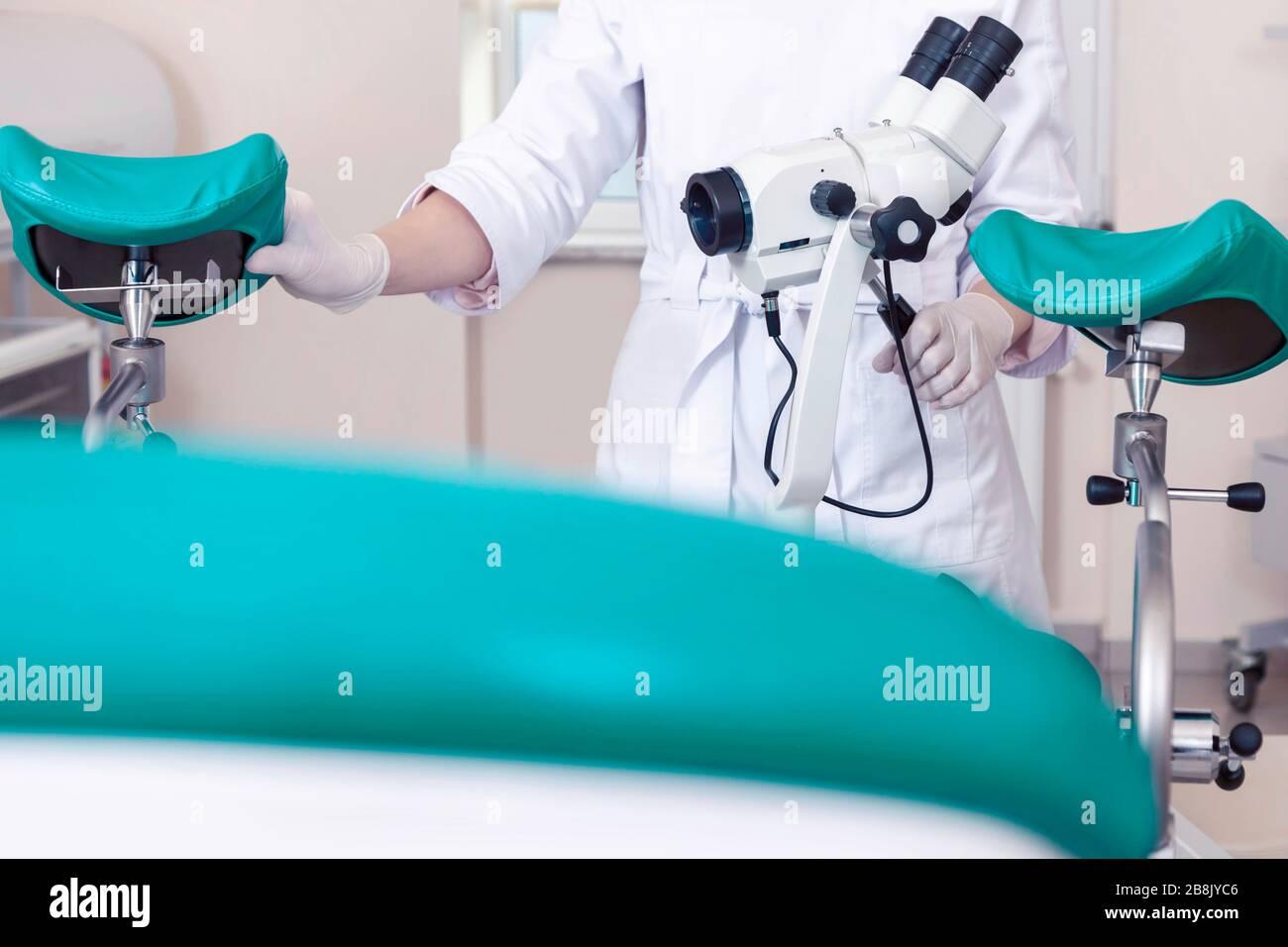 Sala ginecológica con silla y equipo. Manos de la doctora con herramientas para el examen de la salud de la mujer. Foto de stock