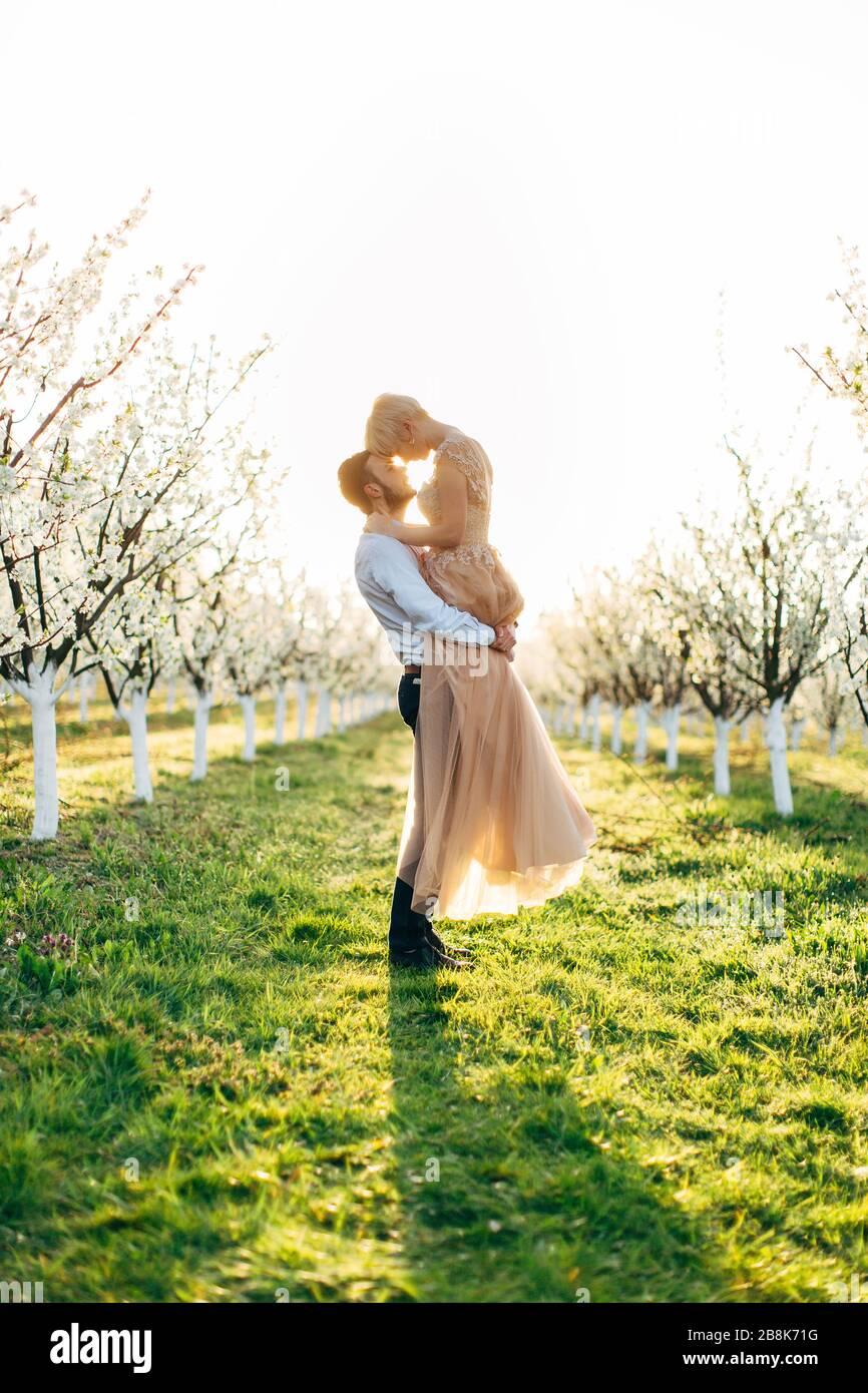 Encantadora pareja cariñosa caminando en un jardín florido de primavera al amanecer. El hombre arrastra a la mujer en sus brazos. Historia de amor, concepto de boda, romántico Foto de stock