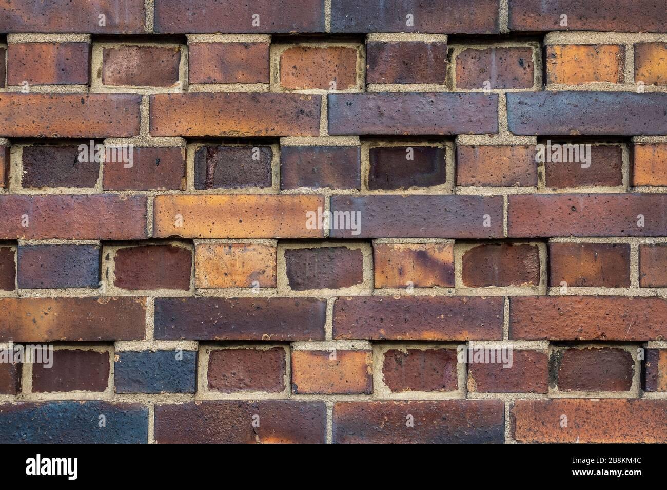 Pared del edificio hecha de ladrillos oscuros, amarillos a marrones del clinker con varios patrones alternantes. Las piedras son desplazadas en filas, giradas, indentadas o om Foto de stock