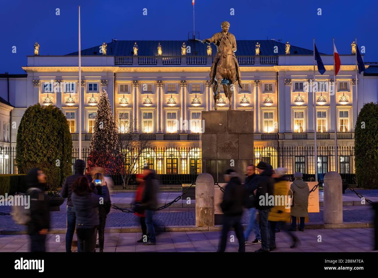 Varsovia, Polonia - 27 de diciembre de 2019: La gente en el Palacio Presidencial iluminado por la noche y Monumento al Príncipe Jozef Poniatowski, monumentos de la ciudad Foto de stock